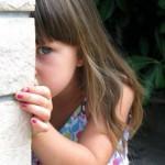 Divorce Helper - Helping children get through divorce and avoid feeling of parental alienation. Girl hiding behind house.